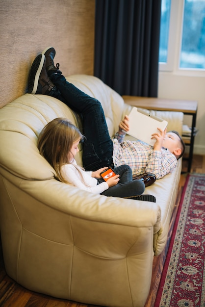 Nahaufnahme eines mädchens, das nahe dem bruder betrachtet digitale tablette auf sofa sitzt Kostenlose Fotos
