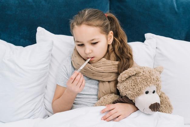 Nahaufnahme eines mädchens, das unter der kälte leidet, die den thermometer in ihren mund einfügt, der auf bett mit weichem spielzeug sitzt Kostenlose Fotos