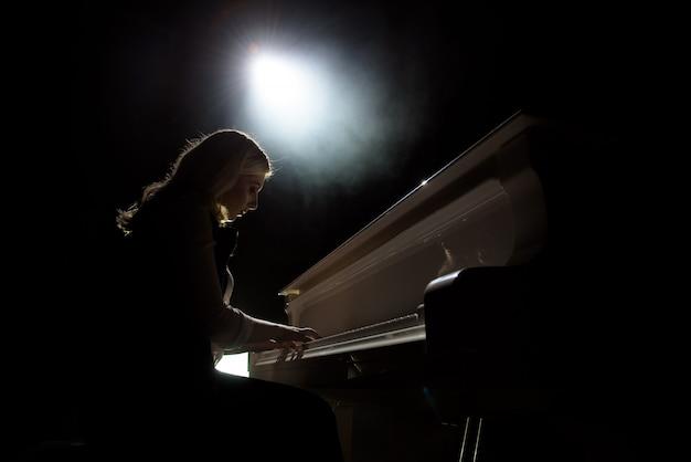 Nahaufnahme eines mädchens spielt klavier im konzertsaal in der szene Premium Fotos