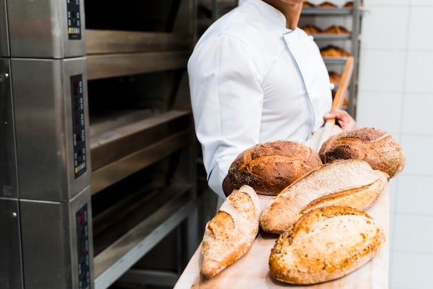 Nahaufnahme eines männlichen bäckers, der frisches gebackenes brot auf hölzerner schaufel vom ofen hält Kostenlose Fotos
