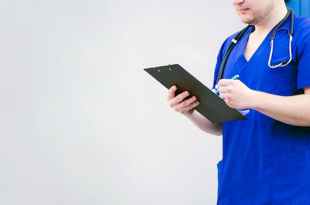 Nahaufnahme eines männlichen doktors, der das klemmbrett mit dem stift lokalisiert gegen grauen hintergrund überprüft Kostenlose Fotos