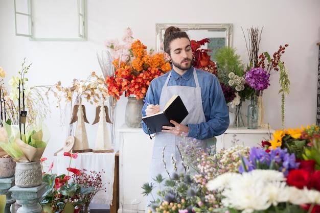 Nahaufnahme eines männlichen floristen, der blumenblumenstraußschreiben im tagebuch mit stift betrachtet Kostenlose Fotos