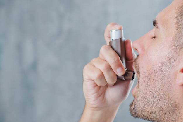 Nahaufnahme eines mannes, der asthmainhalator gegen unschärfehintergrund verwendet Kostenlose Fotos