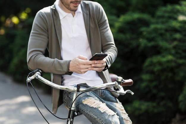 Nahaufnahme eines mannes, der auf dem griff des fahrrades unter verwendung des handys sitzt Kostenlose Fotos