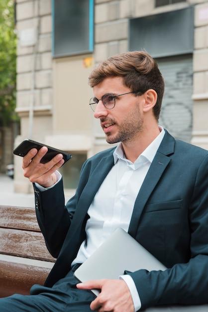 Nahaufnahme eines mannes, der auf der bank spricht am telefon mit dem digitalen sprachassistenten sitzt Kostenlose Fotos