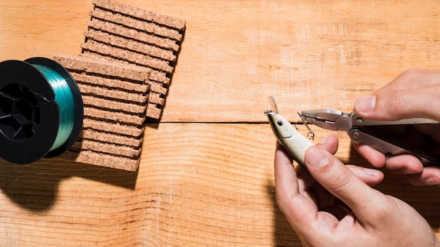Nahaufnahme eines mannes, der den haken mit zange nahe dem spulen- und korkenbrett auf hölzernem schreibtisch repariert Kostenlose Fotos