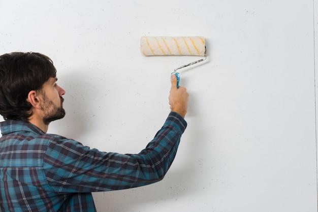 Nahaufnahme eines mannes, der die wand mit farbenrolle malt Kostenlose Fotos