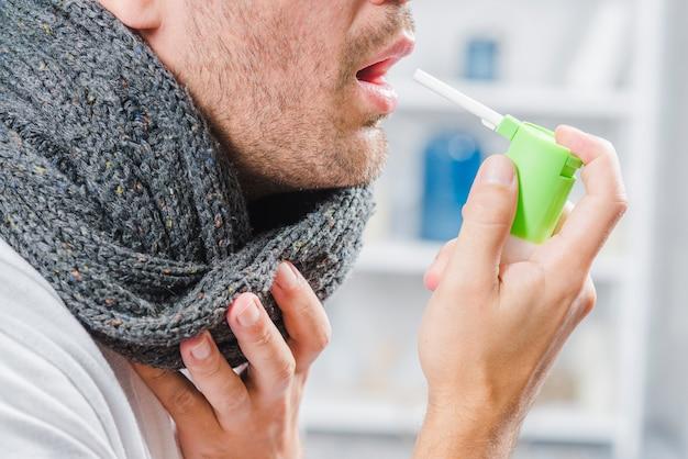 Nahaufnahme eines mannes, der grauen schal um seinen hals unter verwendung eines sprays trägt, um halsschmerzen zu behandeln Kostenlose Fotos