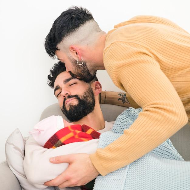 Nahaufnahme eines mannes, der in der hand sein tragendes baby des schlafenden freundes küsst Kostenlose Fotos