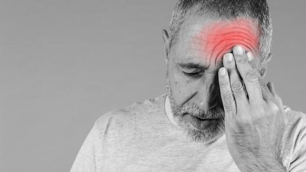 Nahaufnahme eines mannes, der seinen kopf in den schmerz hält Kostenlose Fotos