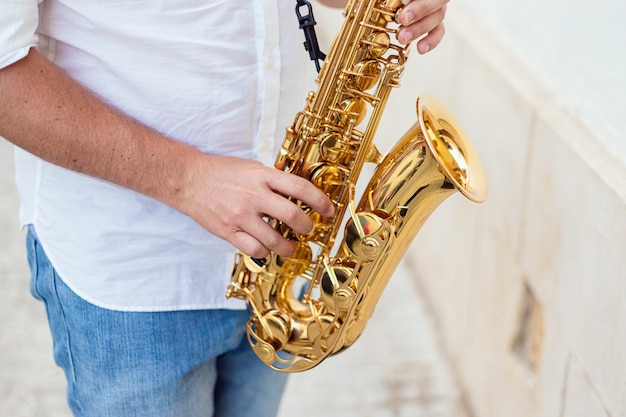 Nahaufnahme eines mannes leidenschaftlich sein saxophon auf der straße zu spielen Premium Fotos