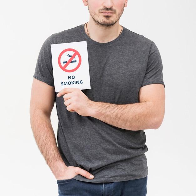 Nahaufnahme eines mannes mit den händen in seiner tasche, die nichtraucherplakat gegen weißen hintergrund zeigt Kostenlose Fotos
