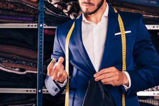 Nahaufnahme eines nähenden gewebes des männlichen modedesigners mit nadel in seiner werkstatt Kostenlose Fotos