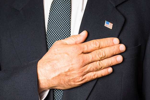 Nahaufnahme eines patriotischen mannes mit usa-abzeichen auf seiner rührenden hand des schwarzen mantels auf seiner brust Kostenlose Fotos