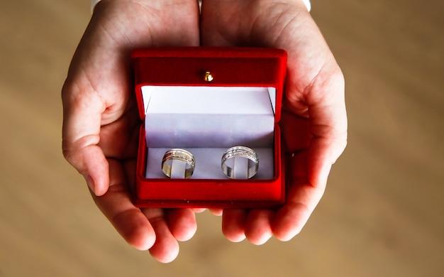 Nahaufnahme eines roten feldes mit zwei ringen für eine verlobung Premium Fotos