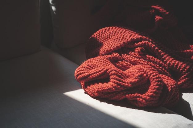 Nahaufnahme eines roten textils auf einer holzoberfläche, die mit dem sonnenlicht beleuchtet wird Kostenlose Fotos