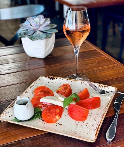 Nahaufnahme eines salats mit käse und tomaten auf einem quadratischen teller mit alkoholischem getränk nahe einer pflanze Kostenlose Fotos