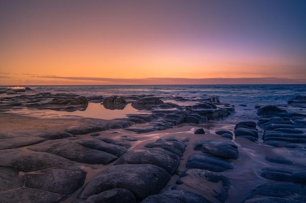 Nahaufnahme eines schönen sonnenuntergangs über der seeküste queensland, australien Kostenlose Fotos