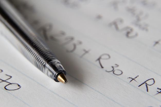 Nahaufnahme eines schwarzen stiftes auf einem stück papier mit einigen zahlen und codes, die darauf geschrieben sind Kostenlose Fotos