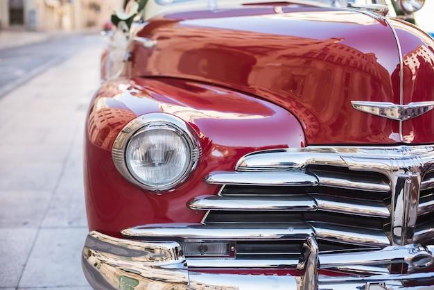 Nahaufnahme eines vorderteils und des scheinwerfers eines roten retro- autos. Premium Fotos