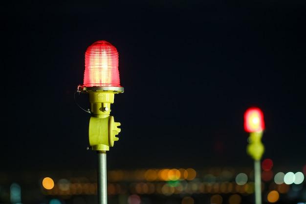 Nahaufnahme eines warnlichts des flugzeuges auf ein hochhaus des gebäudes in der nachtzeit Premium Fotos