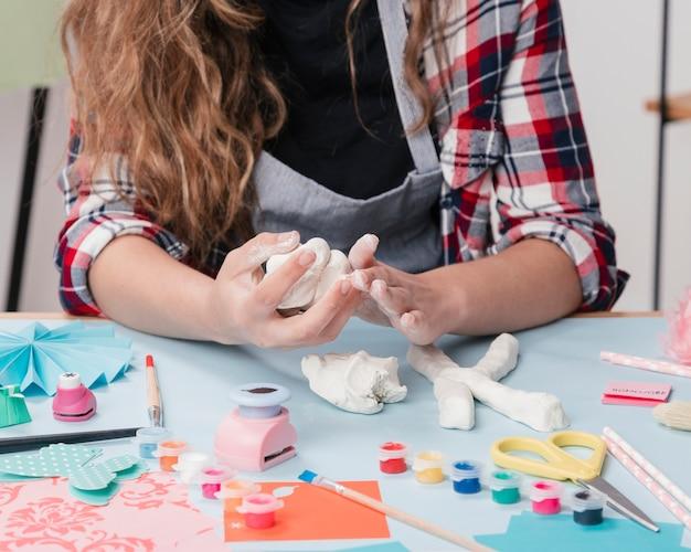 Nahaufnahme eines weiblichen künstlers, der brief mit weißem lehm macht Kostenlose Fotos