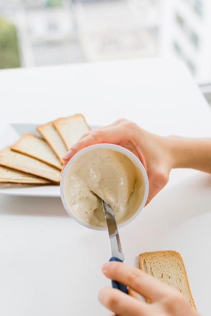 Nahaufnahme eines weiblichen nehmenden käses verbreitete mit messer für das anwenden es auf brot über der tabelle Kostenlose Fotos