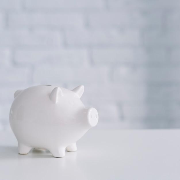 Nahaufnahme eines weißen sparschweins auf schreibtisch Kostenlose Fotos