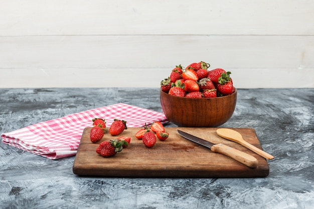 Nahaufnahme erdbeeren und küchenutensilien auf holzschneidebrett mit roter gingham-tischdecke und einer schüssel erdbeeren auf dunkelblauem marmor und weißem holzhintergrund. horizontal Kostenlose Fotos