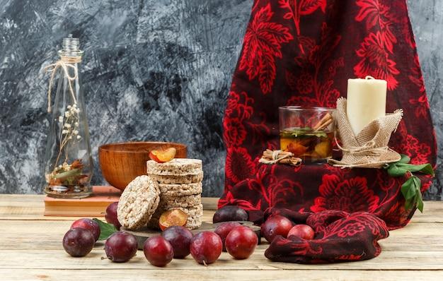 Nahaufnahme fermentiertes getränk und kerze auf rotem schal mit waffeln, krugvase, einer schüssel, pflaumen und rotem schal auf holzbrett und dunkelgrauem marmorhintergrund. horizontaler freier speicherplatz für ihren text Kostenlose Fotos