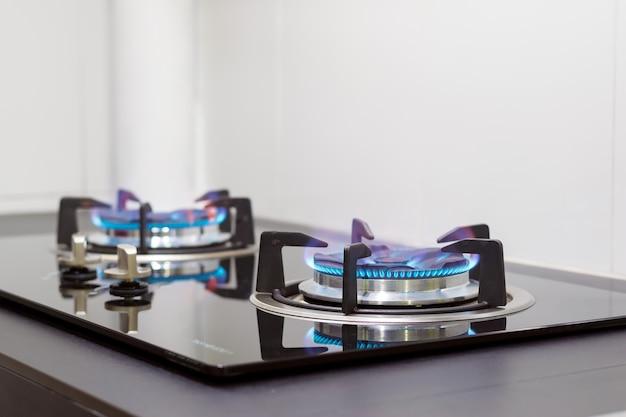 Nahaufnahme flammen vom gasherd eingebettet in den zähler in der küche. Premium Fotos
