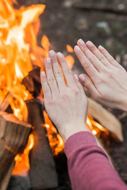 Nahaufnahme frau, die am lagerfeuer wärmt Kostenlose Fotos