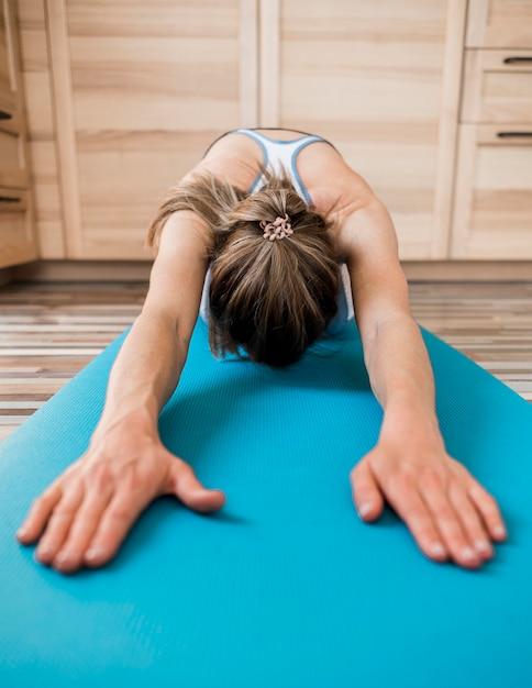 Nahaufnahme frau, die auf yogamatte streckt Kostenlose Fotos