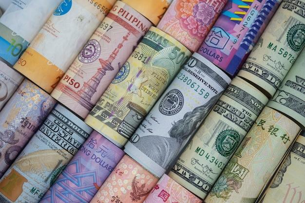 Nahaufnahme gerollt von der vielzahlbanknote auf der ganzen welt. wechselkurs und forex-anlagekonzept Premium Fotos