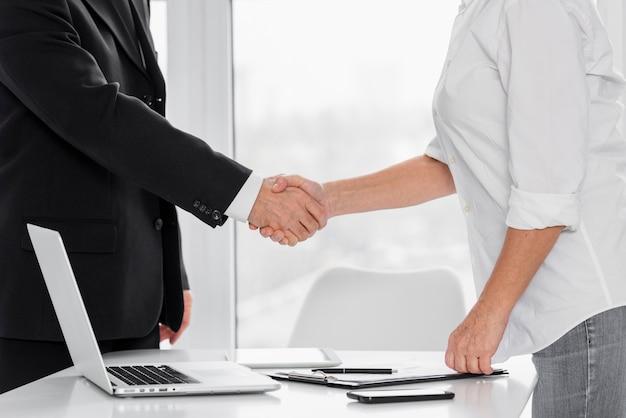 Nahaufnahme geschäftlicher handschlag im büro Premium Fotos