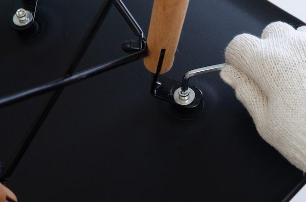 Nahaufnahme geschossen, hand des schraubenden weges des tischlers der stühle mit hexeschlüssel Premium Fotos