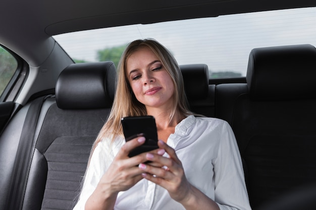 Nahaufnahme geschossen mit blondinen, die telefon betrachten Kostenlose Fotos