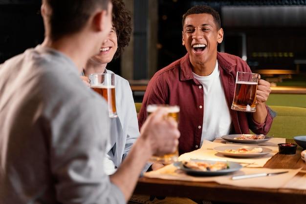 Nahaufnahme glückliche männer mit bierkrügen Kostenlose Fotos