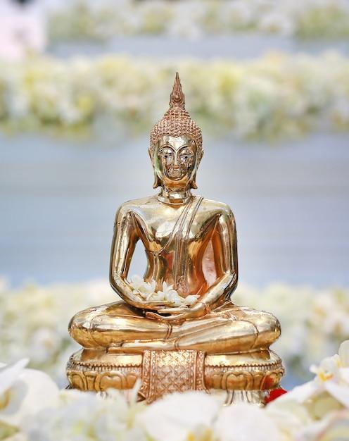 Nahaufnahme goldene buddha-statue mit blume herum. Premium Fotos