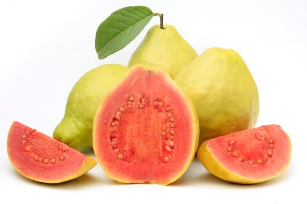 Nahaufnahme guajava-frucht, rosa, frisch, organisch, mit den blättern, ganz und geschnitten, lokalisiert auf weißem hintergrund. vorderansicht Premium Fotos