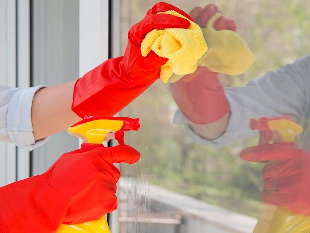 Nahaufnahme hände mit gummihandschuhen das fenster reinigen Kostenlose Fotos