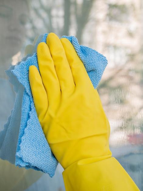 Nahaufnahme hand mit gummihandschuh reinigungsfenster Kostenlose Fotos