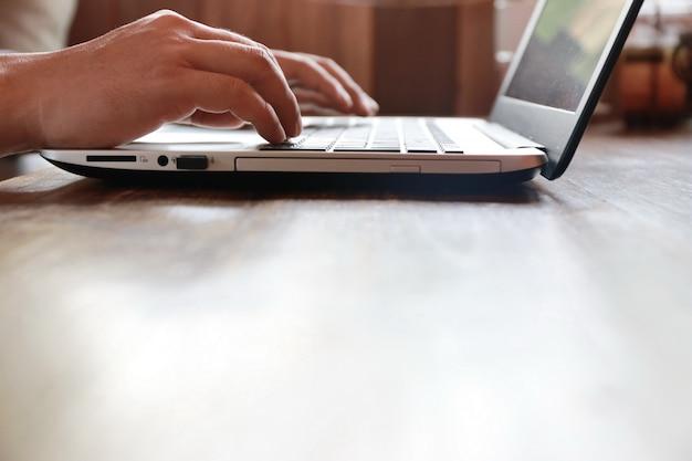 Nahaufnahme hand und finger laptop tastatur auf holztisch mit textfreiraum eingeben Premium Fotos