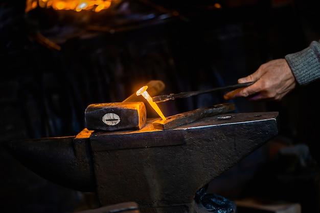 Nahaufnahme heißer metallnagel auf einem amboss in der schmiedewerkstatt Premium Fotos