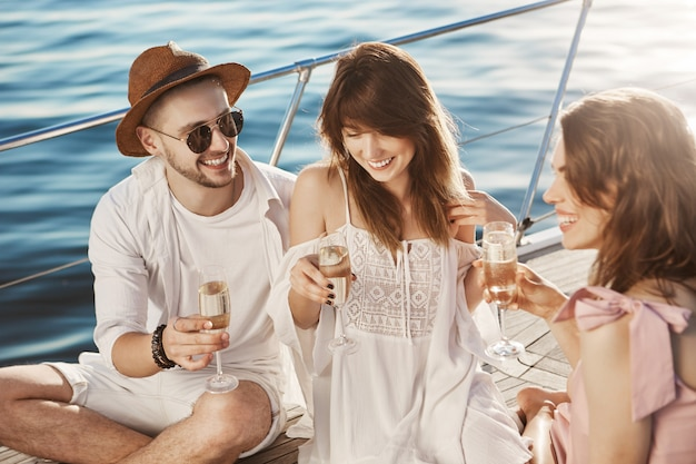 Nahaufnahme im freien porträt von drei freunden sprechen und champagner trinken, während an bord des bootes sitzen und sonnenlicht genießen. Kostenlose Fotos