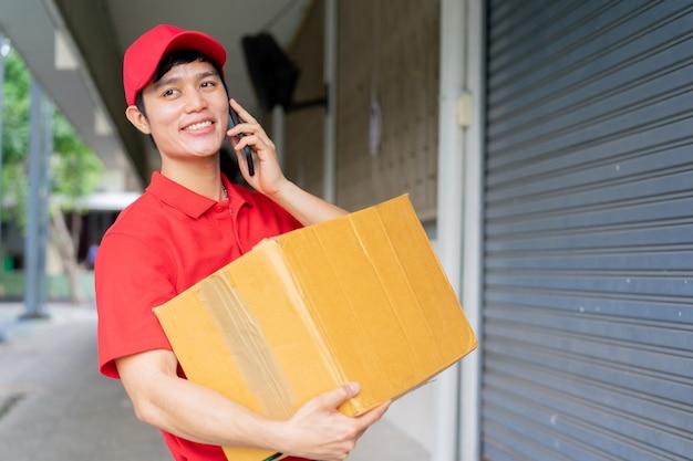 Nahaufnahme junge postangestellte (mit roter uniform) tragen box und stehen vor dem haus und mit smartphone an den kunden für die bestellung Premium Fotos