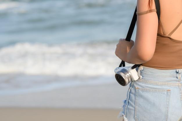 Nahaufnahme junge touristische frau, die kamera am strand und an der seelandschaft hält. Premium Fotos