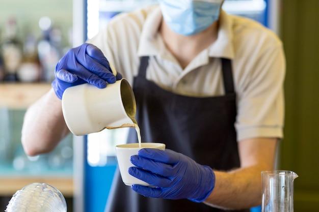 Nahaufnahme kellner mit handschuhen kaffee vorbereiten Kostenlose Fotos