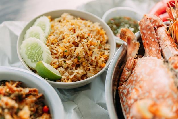 Nahaufnahme-krabbe fried rice mit gurke und kalk und gedämpfte blumenkrabben dienten mit würziger meeresfrüchtesoße der thailändischen art. Premium Fotos