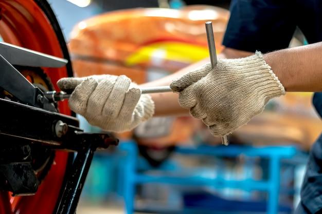 Nahaufnahme, leute reparieren ein motorrad verwenden sie einen schraubenschlüssel und einen schraubenzieher, um zu arbeiten. Premium Fotos